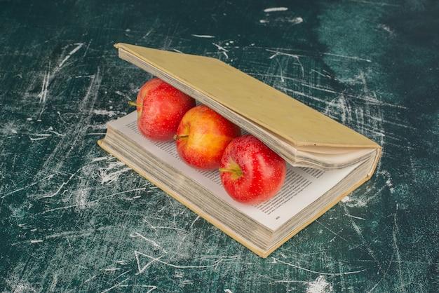 Mele all'interno di un libro sulla superficie di marmo con un coltello.