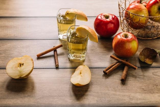 Apples, juice, cinnamon sticks on wooden background