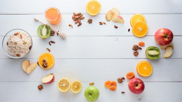 Яблоки, киви, сухофрукты, апельсины и яблоки. концепция здорового питания. застрелен на белом деревянном столе.
