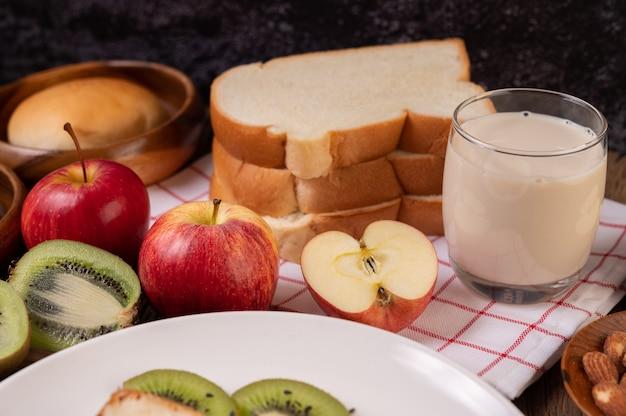 赤白い布の上のプレートにリンゴ、キウイ、牛乳、パン