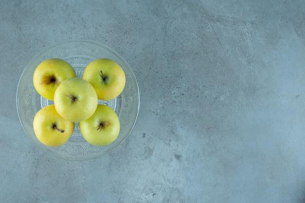 Яблоки на стеклянном постаменте, на мраморном фоне. фото высокого качества