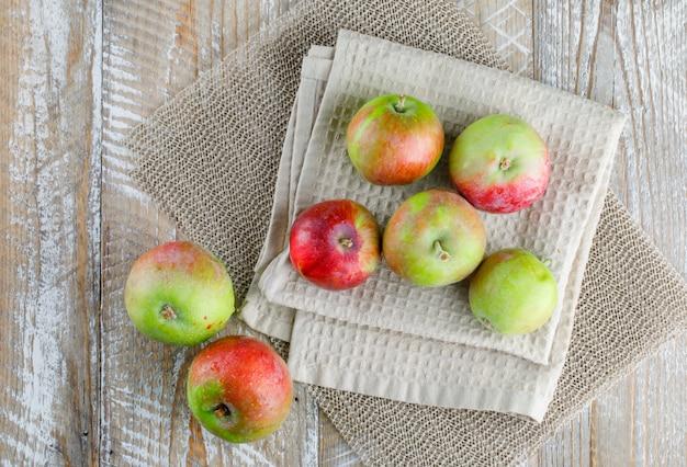 木製のキッチンタオルとプレースマットの上のリンゴ。