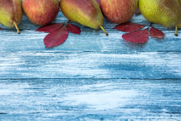 Apples, pears and autumn leaves on wooden background. autumn background