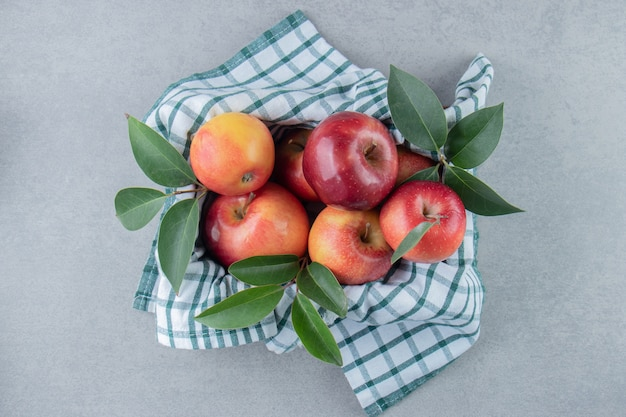 Apples piled in a basket covered with a towel on marble