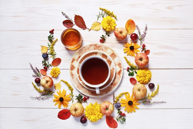 Apples, plums, fresh honey, tea cup, red berries and beautiful flowers