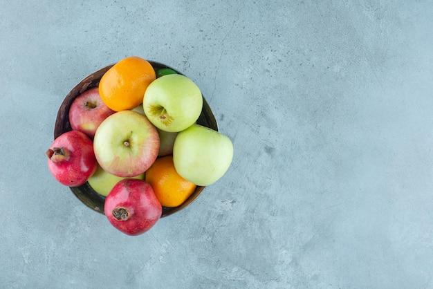 Яблоки, гранат и мандарины в серебряной миске.