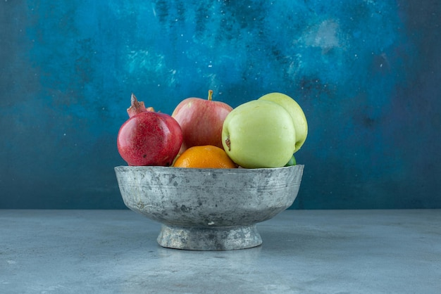 Mele, melograno e mandarini in una ciotola d'argento.
