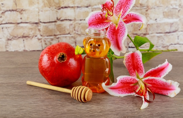Apples, pomegranates and honey on a vintage dish in the kitchen. wooden table. the traditional setting for the jewish new year - rosh hashanah.