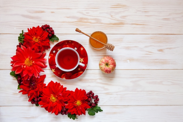 Apples, red dahlia flowers, red rowanberries and honey with copy space