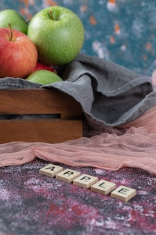 Apples in a rustic wooden tray on a kitchen towel