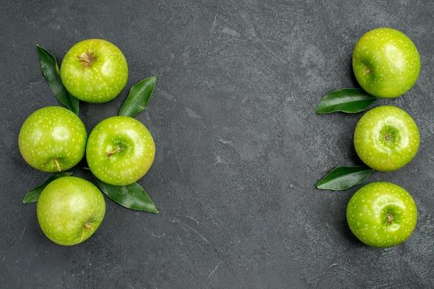 暗いテーブルの上に葉を持つリンゴ7つの食欲をそそるリンゴ