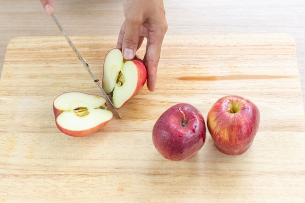 Apples and slices on wooden cutting board.