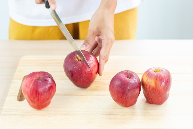 Apples and slices on wooden cutting board..