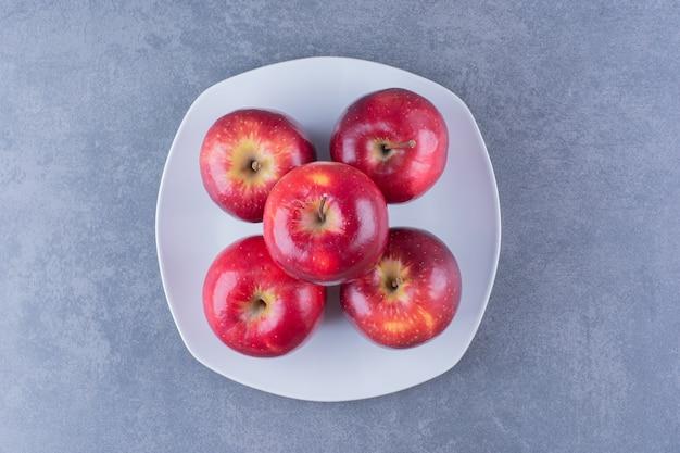 Яблоки, сложенные друг на друга на тарелке, на темной поверхности