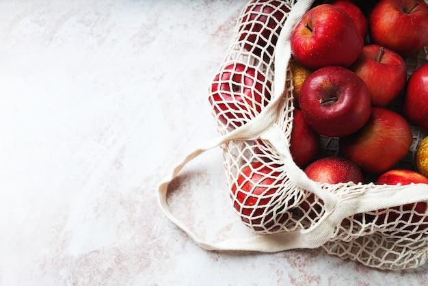 Яблоки в сетке. концепция устойчивого развития и осознанного потребления. вид сверху. flat lay