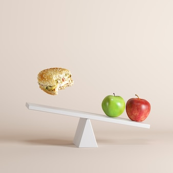 An apples tipping seesaw with floating bergers on opposite end on pastel background.
