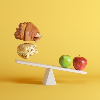 An apples tipping seesaw with floating bergers and pork leg on opposite end on yellow background.