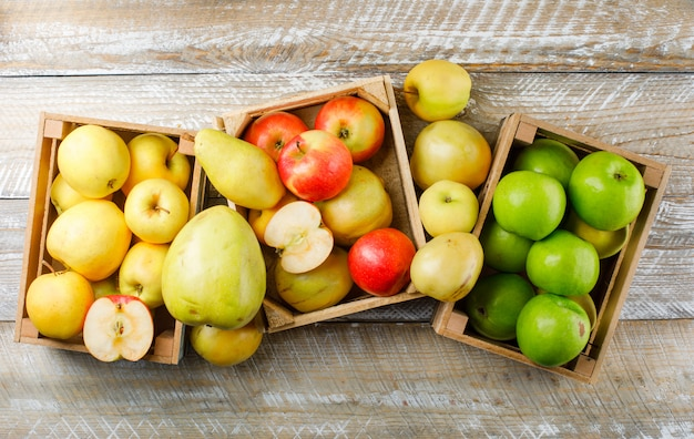 Apples variety with pears in wooden boxes on wooden