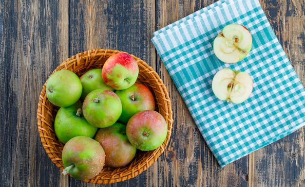 Apples in a wicker basket on wooden and picnic cloth background. top view.