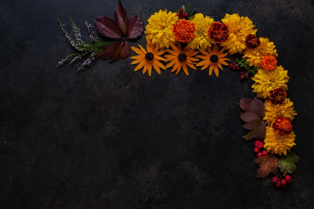 Apples, wild cherry-plums, red berries and beautiful autumn flowers with copy space floral decoration.