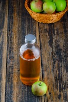 木製の背景、ハイアングルでバスケットに飲み物のボトルとリンゴ。 無料写真