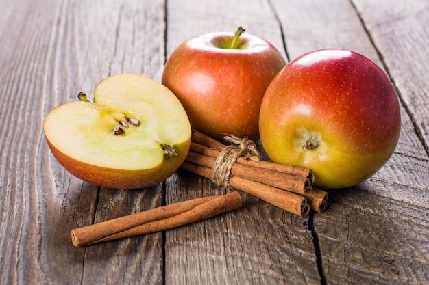 木製のテーブルにシナモンとリンゴ