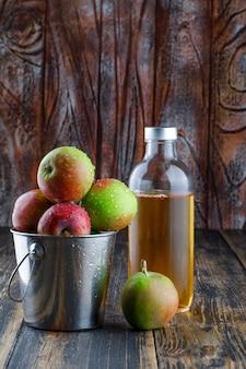古い木製の背景、側面図のミニバケツで飲み物とリンゴ。