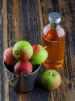 木製の背景、高角度のビューのミニバケツで飲み物とりんご。 無料写真