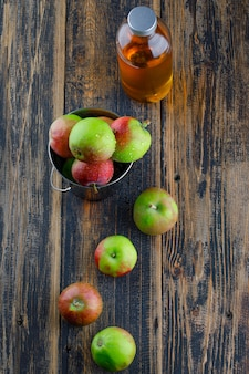 木製の背景、上面にミニバケツで飲み物とりんご。 無料写真