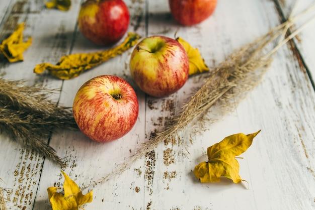 ぼろぼろのテーブルの上の乾燥葉とりんご