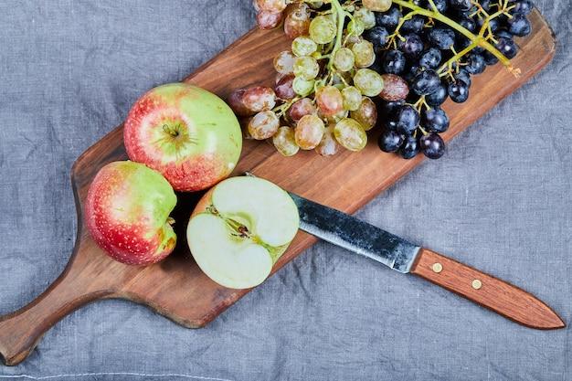木の板に緑と赤のブドウとリンゴ。