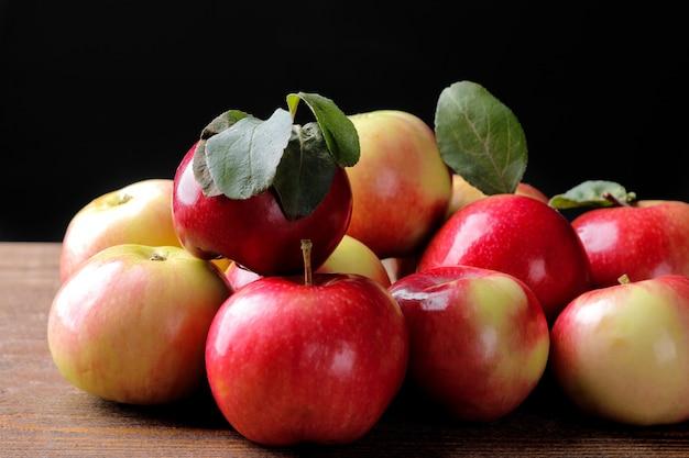 木製のテーブルの緑の葉とリンゴ