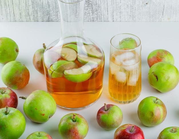 Яблоки с соком под высоким углом зрения на белом и шероховатом