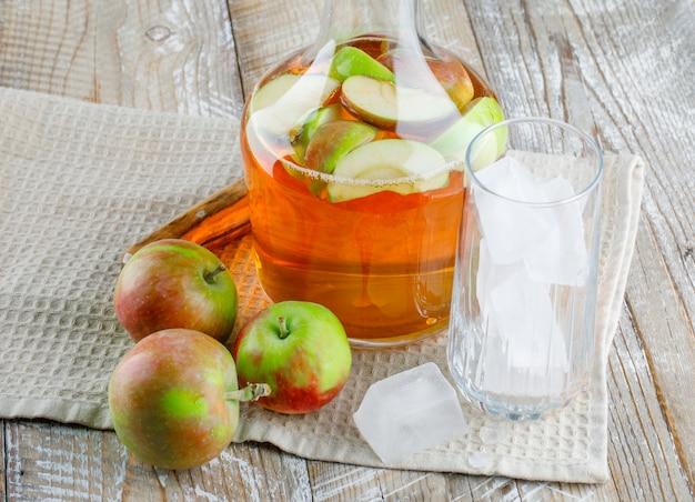 Яблоки с соком, кубики льда в стакане, крупный план ножа на деревянном и кухонном полотенце