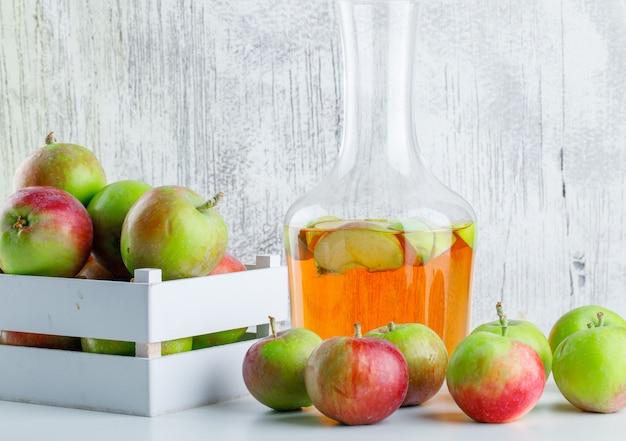Яблоки с соком в деревянной коробке на белом и шероховатом, вид сбоку.