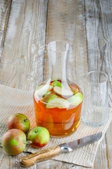Яблоки с соком, ножом, стеклом на деревянном и кухонном полотенце, высокий угол обзора.