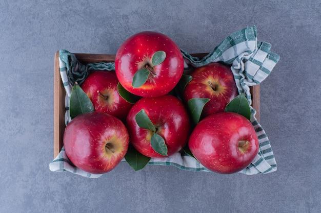 어두운 표면에 상자에 수건에 잎 사과