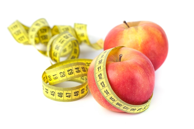 Apples with measure tape on white background, healthy diet.