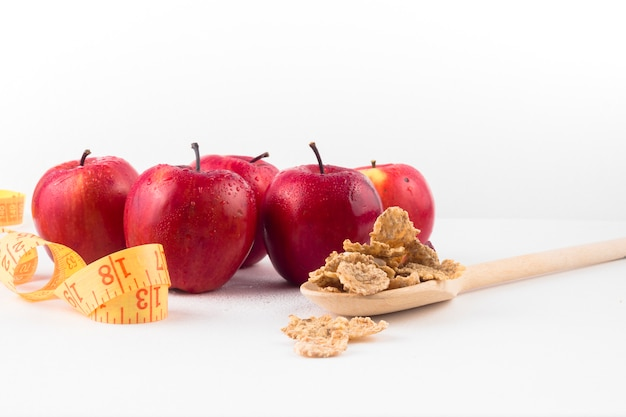 Apples with measuring tape and cereals on spoon
