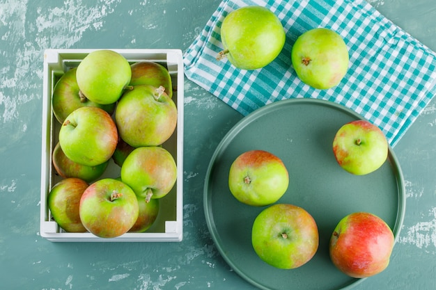 Apples in wooden box and tray on plaster and picnic cloth background. flat lay.