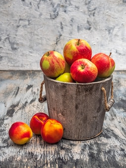 Apples in a wooden bucket and nectarines on a gray background close up