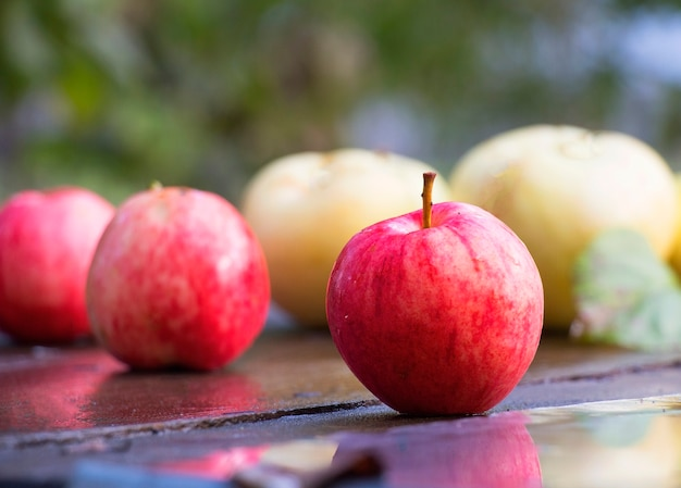 Apples on a wooden table after a rain