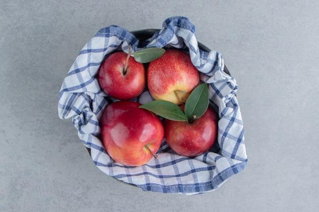 大理石にタオルで包まれたリンゴ。