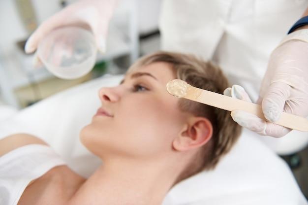 Нанесение прозрачного обезболивающего геля на лицо женщины, чтобы сделать процедуру лазерной эпиляции безболезненной. профессиональное лазерное лечение в современной спа-клинике. сосредоточьтесь на деревянном шпателе