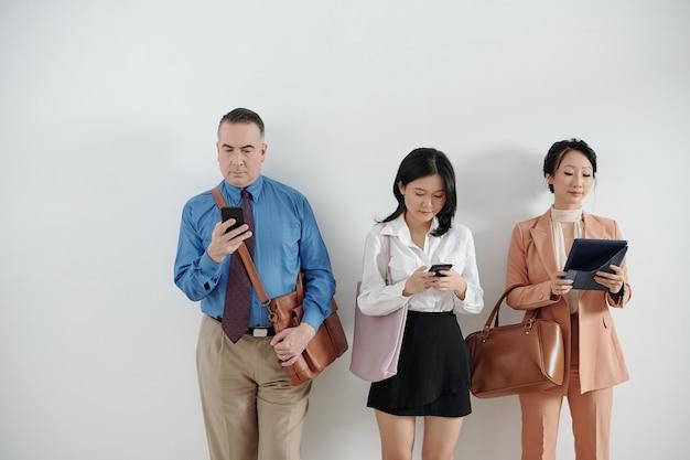 대기줄에 서서 면접을 기다리고 스마트폰과 태블릿에서 소셜 미디어를 확인하는 지원자