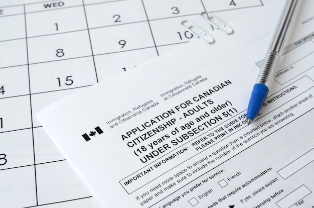 Application for canadian citizenship for adults and blue pen lies on calendar page