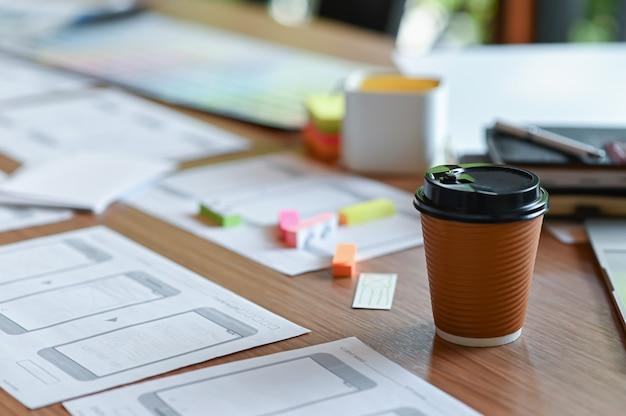 Приложение-стол с дизайнерским эскизом мобильного телефона и кофе на вынос в домашнем офисе