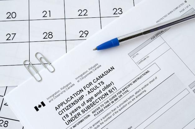 성인과 파란색 펜을위한 캐나다 시민권 신청은 달력 페이지에 있습니다.