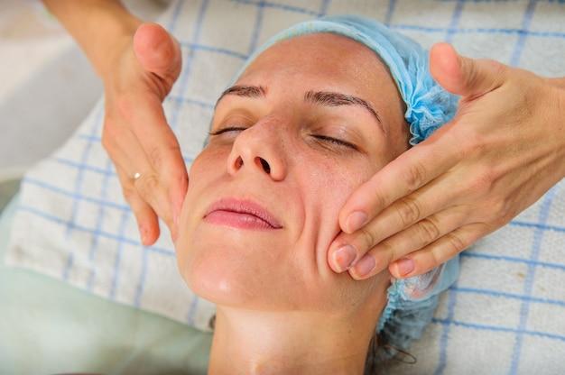 Нанесение золотых масок на лицо модели. косметические процедуры.