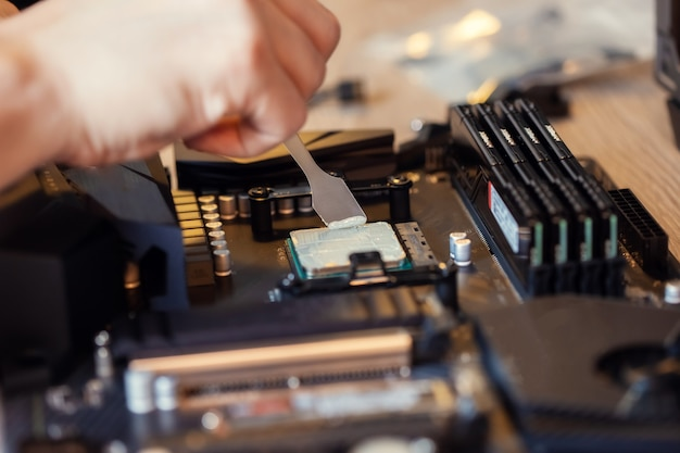 Application of thermal paste on the computer processor chip for high-quality cooling. spreading of thermal paste with a special spatula